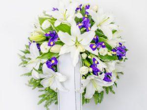 Matusepärg kuuseoksal valgete liiliate ja siniste lilledega