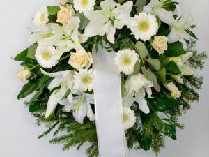 Matusepärg kuuseokstel valgete ja kreemide lilledega